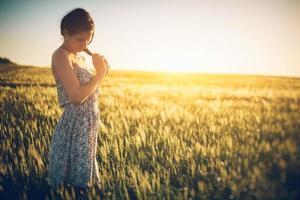 mulher jovem e bonita no campo de trigo primavera foto