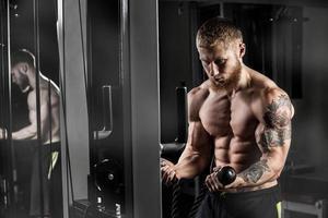fisiculturista muscular do atleta no ginásio treinando com bar