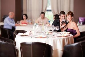 casal feliz na mesa do restaurante brindando foto