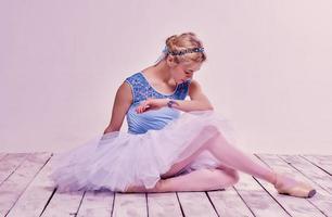 cansada bailarina sentada no chão de madeira