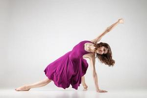 jovem bailarina usando vestido roxo sobre cinza