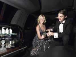 casal desfrutando de champanhe na limusine foto