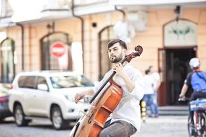 cara que toca violoncelo na rua no verão foto