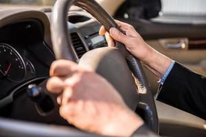 um homem de terno segurando uma roda cinza dirigindo foto