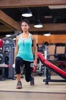 treino de mulher com halteres no ginásio de fitness foto