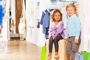 menino fica e menina senta-se com sacolas de compras foto