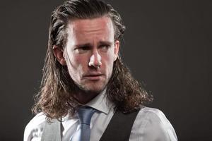 jovem rosto expressivo de cabelos longos, vestindo terno e gravata.