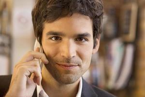 homem bonito, ligando com um telefone celular no café bar