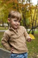 o garoto com uma folha amarela foto