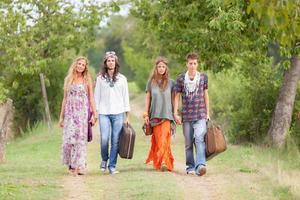 grupo hippie andando em uma estrada rural