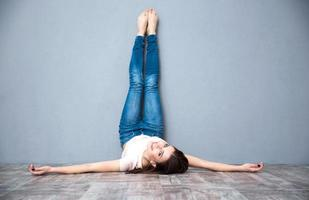mulher deitada no chão com as pernas levantadas foto