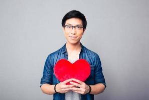 homem asiático segurando coração vermelho foto