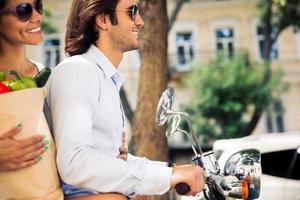 casal jovem feliz, montando uma scooter