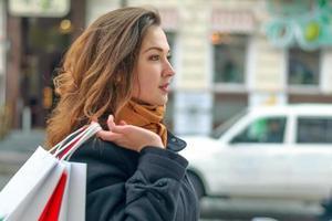 menina caminha ao longo de uma rua da cidade com sacolas de compras foto