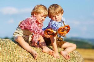 dois meninos irmãos e amigos sentado na pilha de feno foto