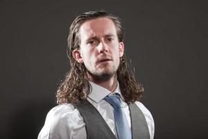 jovem rosto expressivo de cabelos longos, vestindo terno e gravata. foto
