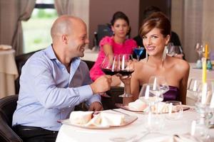 jovem casal brindando a mesa do restaurante foto