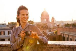 jovem feliz com câmera fotográfica na rua em Roma