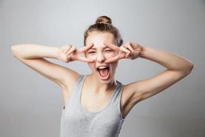 closeup retrato jovem mulher com dedos v no rosto foto