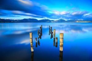 cais de madeira, cais permanece em um lago azul pôr do sol, céu