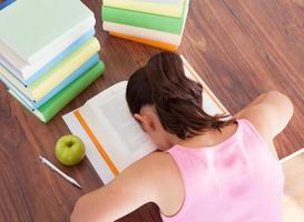 estudante cansada, dormindo no livro foto