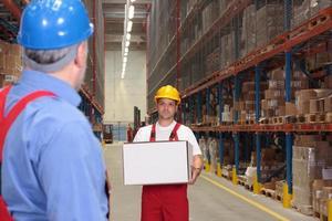 trabalhador em uniforme e capacete carregando caixa