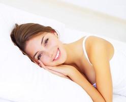 menina sorridente, deitada na cama foto