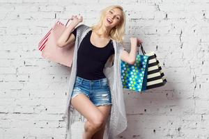 adorável menina loira contra a parede com sacolas de compras novas foto