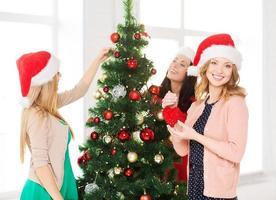 mulheres em chapéus de ajudante de Papai Noel a decorar uma árvore