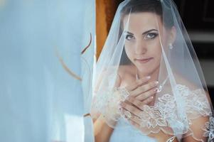 noiva linda se preparando no vestido de casamento branco com penteado foto