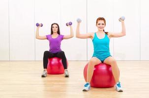 duas mulheres desportivos no clube de fitness foto