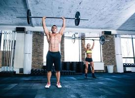 grupo de mulher e homem treino com barra foto