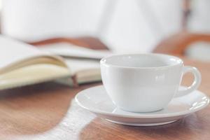 xícara de café branco com notebook foto