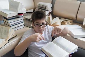menino de óculos, lendo um livro no quarto