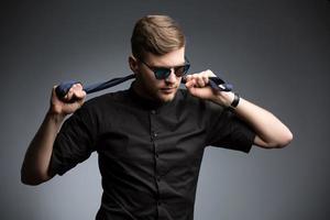 homem elegante de camisa preta e óculos de sol espelhados foto
