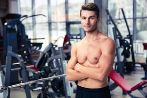homem de pé com os braços cruzados no ginásio foto