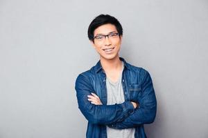 retrato de um homem asiático feliz com os braços cruzados foto