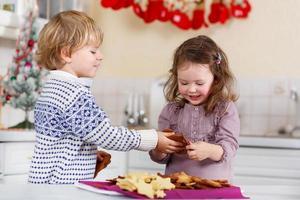 menino e menina fazendo biscoitos de natal em casa foto