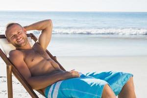 sorridente homem bonito, banhos de sol em sua cadeira de praia foto