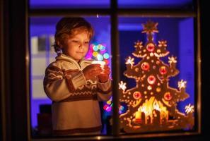 menino sorridente parado pela janela na época do Natal foto