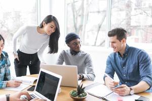 jovens profissionais trabalhando em laptops em um escritório