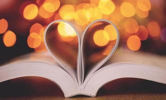 páginas do livro em forma de coração com bokeh de fundo foto