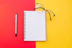 caderno, óculos e caneta em fundo vermelho e amarelo