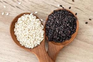sementes de gergelim preto e branco em colheres de madeira foto