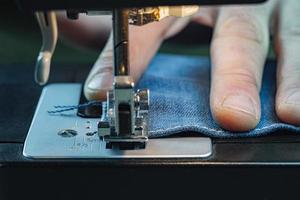 jeans de costura de mão masculino em uma máquina de costura foto