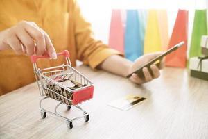 mulher de compras on-line com smartphone segurando um pequeno carrinho de compras