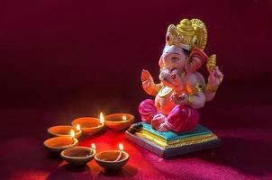lâmpadas de diya de barro acesas com o senhor ganesha durante a celebração do diwali foto