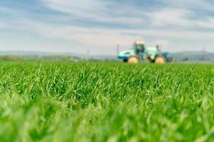 alto campo de grama com trator turva foto