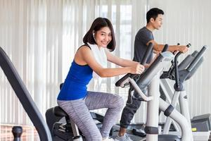 mulher e homem exercitando na academia foto