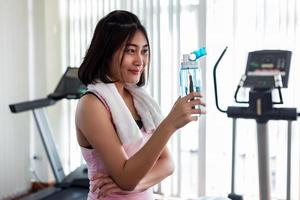 mulher com garrafa de água na academia foto